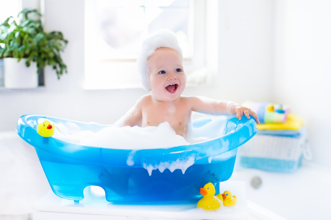 Funny image of baby in the bath with soap suds on top of head.